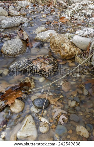 Small Autumn creek with colorful leaves and stones