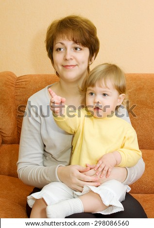Small baby and mother on armchair in home - stock photo