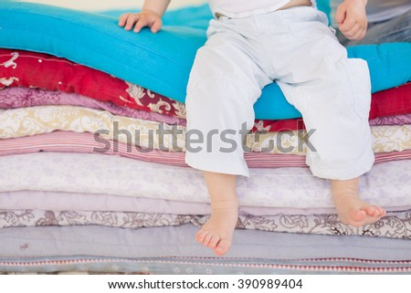 Small baby boy in white trousers sitting on a pile of colorful blankets and mattresses. Happy childhood. Leisure. Indoors. barefoot boy in the bedroom or kids room.  - stock photo
