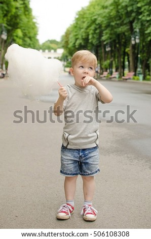Small baby boy is eating cotton candy in the park