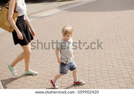 Small baby boy is having fun in the park with his mother
