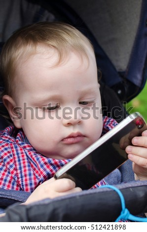 Small baby boy is playing with the cellphone in the park