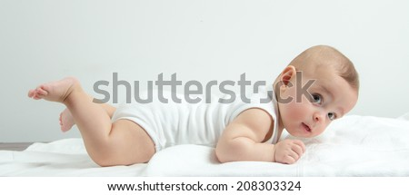 Small baby boy lying on stomach and raising his head and legs upwards while looking surprised and smiling cute - stock photo