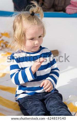 small baby boy or cute child with happy face and blonde hair in stripped shirt and pants sitting sunny summer outdoor