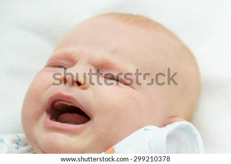 small baby crying and smiling on white - stock photo