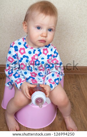 Small baby girl, is sitting on a pink pot and drinks water from a bottle - stock photo