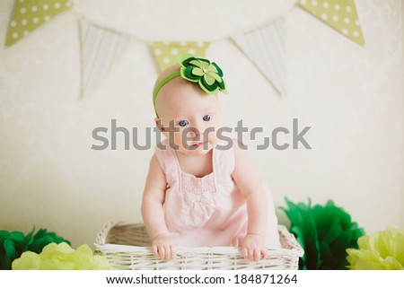 Small baby girl sitting and smiling in the white box in decorated zone