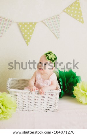 Small baby girl sitting in the white box in decorated zone