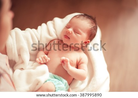 Small baby girl sleeping on mothers hands closeup. Top view. Woman holding infant girl. Motherhood.  - stock photo