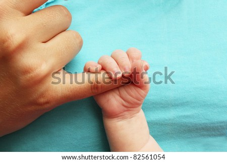 Small baby holding parents hand on blue background