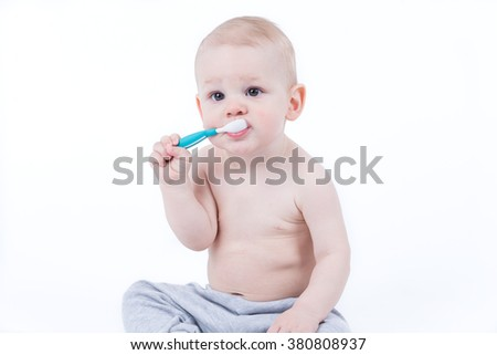 Small baby is training eating with plastic spoon