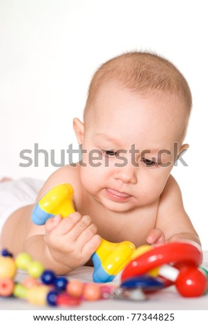 small baby playing with toys on bed