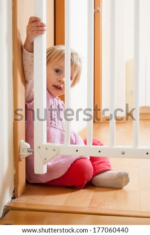 Small baby sitting near safety gate  at home - stock photo