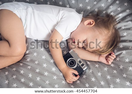 Small baby sleeping in his bed and holding camea, dreaming about his future as a photographer. - stock photo