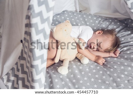 Small baby sleeping in his bed, dreaming. Nightime. Teepee. - stock photo