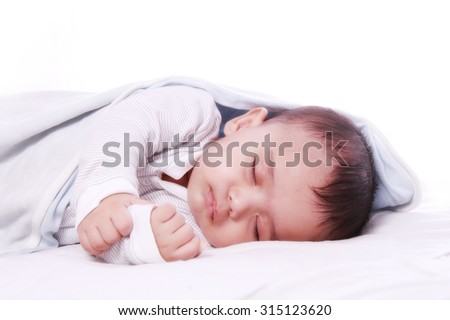 Small baby sleeping  , under white blanket and photographed against white background - stock photo