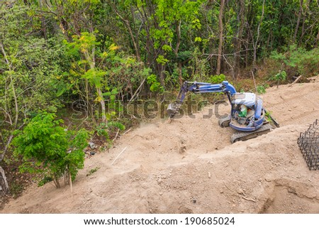 small backhoe tractor works in construction site - stock photo