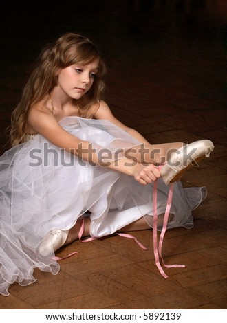 Small ballerina putting on pointes