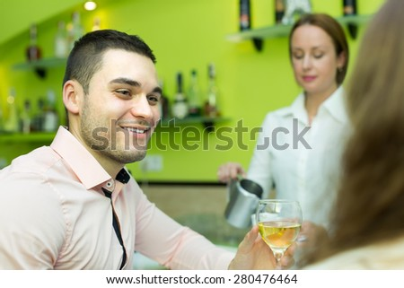 Small bar with female barista and two clients at counter. Focus on man - stock photo