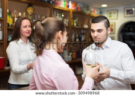Small bar with smiling female barista and two clients at counter - stock photo