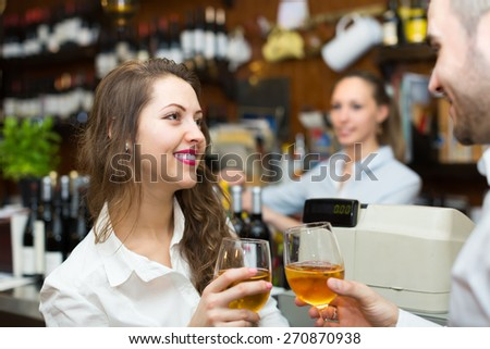 Small bar with young female barista and two clients at counter - stock photo