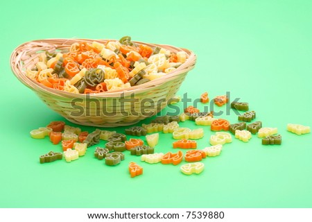 small basket with assorted colorful uncooked pasta on green background