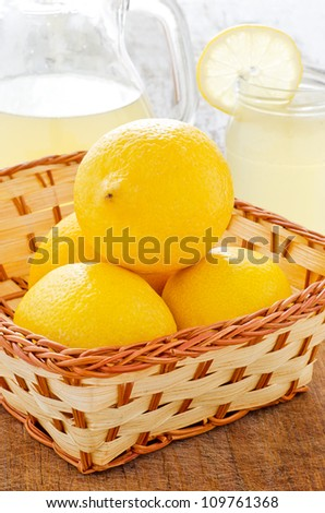 Small basket with fresh lemons and lemonade in the background - stock photo