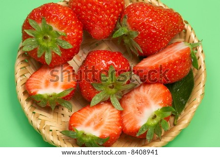 small basket with fresh strawberries on green background