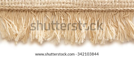 Small bathroom carpet of rough textile with fringe