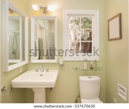 Small Bathroom in luxury home with green walls, mirrors and view window.  - stock photo