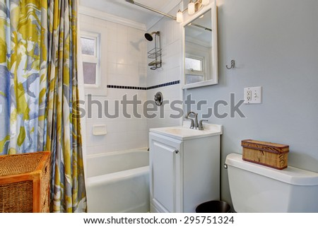 Small bathroom with colorful shower curtain, and lovely blue walls.