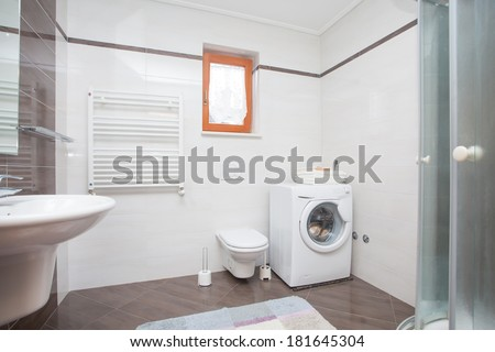 small bathroom with shower and washing machine - stock photo