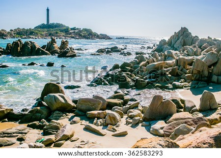 Small bay surrounded by stones near Ke ga lighthouse in Phan Thiet region, Vietnam.  blue water and huge colorful stones in the front, horizontal