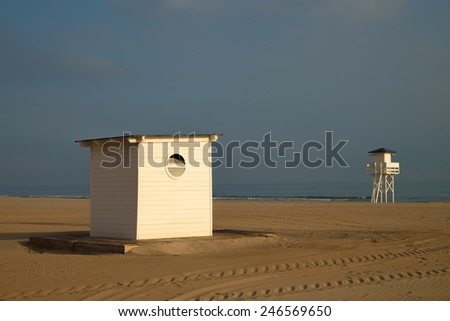 Small beach hut and lifeguard tower on a sandy beach - stock photo