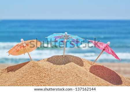 Small beach umbrellas on a beach on a background of the sea. - stock photo