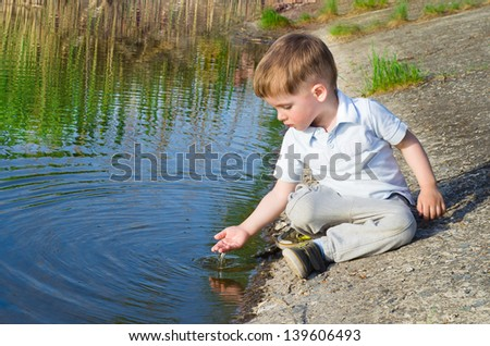 Small beautiful boy pours water from the palm on the river