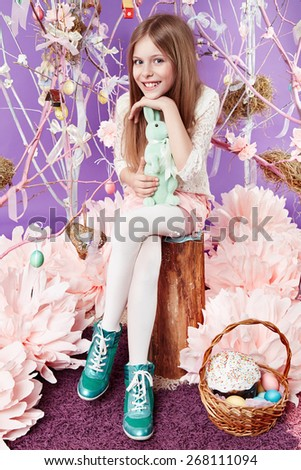 Small beautiful cute  blonde girl holding Little fluffy Easter bunny sitting in a wicker basket on a background of violence sky and spring trees with flowers eggs - stock photo