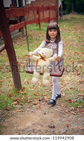 Small beautiful girl and amusing bear - stock photo