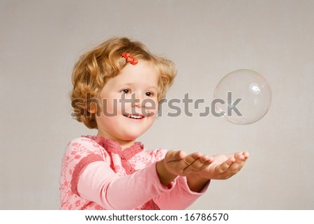 Small beautiful girl looking at a soap bubble - stock photo