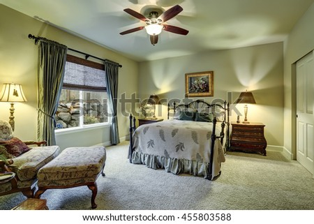 Small bedroom with beige walls, carpet floor and home office area  - stock photo