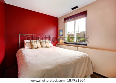 Small bedroom with red and cream wall. Iron frame bed with tropical theme bedding - stock photo