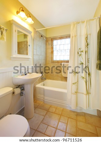 Small beige bathroom with walk in white shower and white cabinet. - stock photo