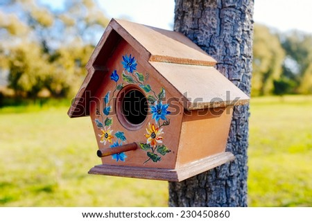 small birdhouse hanging from a tree - stock photo