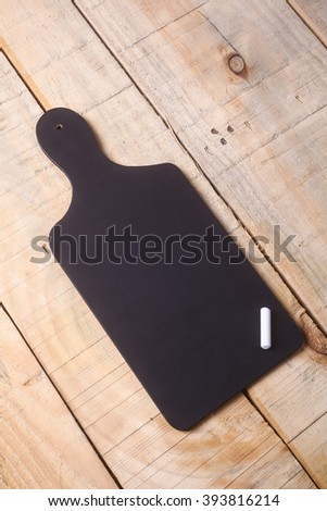 Small black blank chalkboard with pieces of chalk on a grunge wooden surface