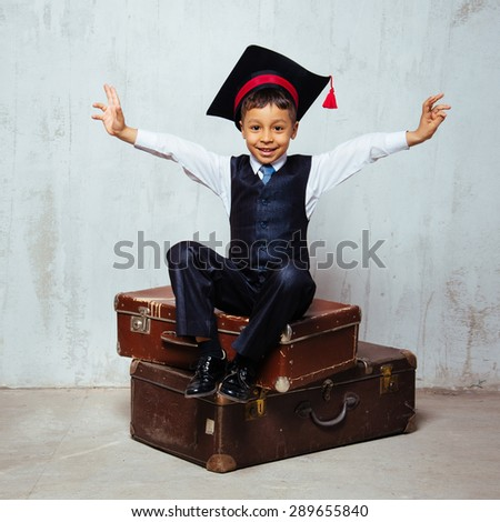 small black boy in  graduation hat sits on the old suitcases and swing hands wants to hug everybody.  instagram toned - stock photo