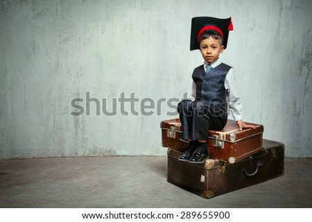 small black boy in suit and graduation hat sits on the old suitcases and look into the camera. copy space left, instagram toned - stock photo
