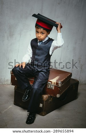 small black boy in suit and graduation hat sits on the old suitcases and look left. instagram toned - stock photo