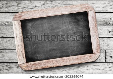 Small black chalkboard on wood background - stock photo