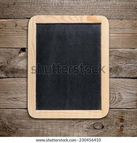Small blackboard on old wood background - stock photo