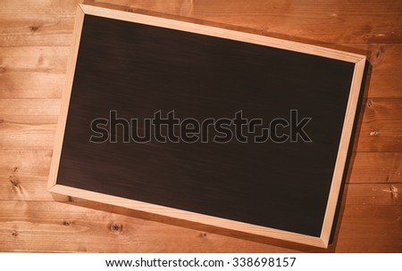 Small blackboard on wooden floor with copy space